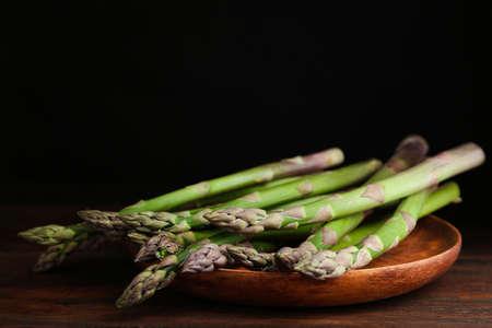 Fresh raw asparagus on wooden table, closeup