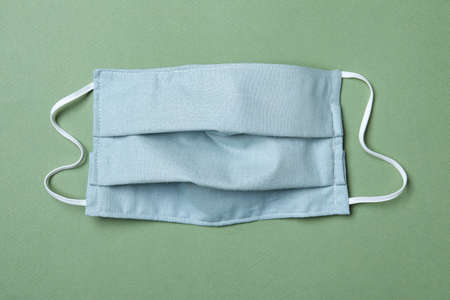 Homemade protective mask on gray-green background, top view. Sewing idea Reklamní fotografie