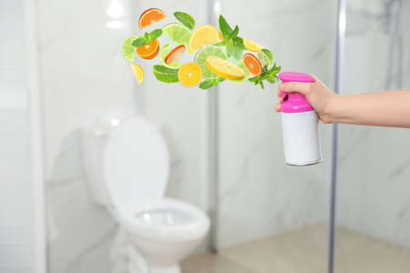 Woman spraying air freshener in bathroom, closeup. Citrusy and minty aroma
