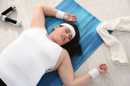 Lazy overweight woman sleeping instead of training on mat at gym, above view Banco de Imagens
