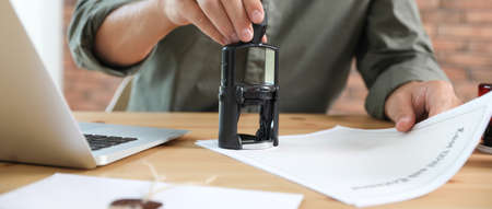 Male notary stamping document at table in office, closeup. Banner design