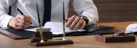 Male notary working at table in office, closeup. Banner design