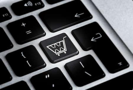 Modern laptop keyboard with cart symbol, closeup view. Internet shopping