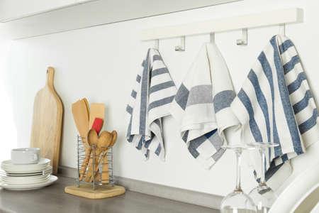 Différents torchons de cuisine suspendus à un support à crochets à l'intérieur Banque d'images