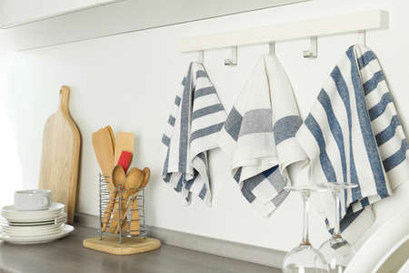Different kitchen towels hanging on hook rack indoors Stock Photo
