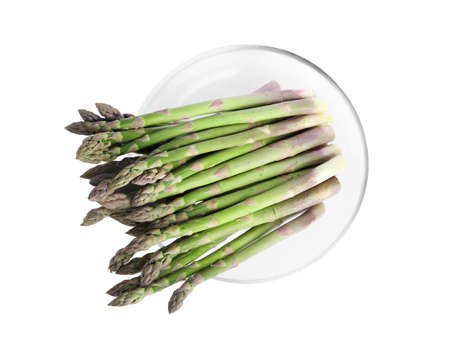 Raw asparagus in glass bowl isolated on white, top view