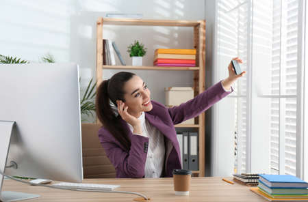 Lazy employee taking selfie at table in office