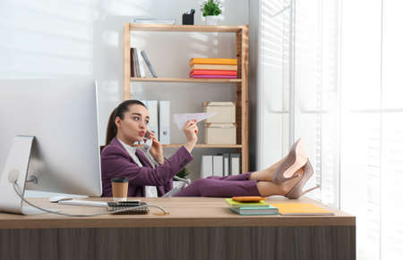 Lazy employee playing with paper plane in office