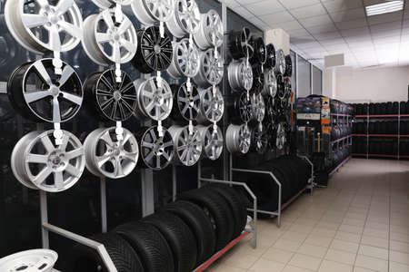 Car tires and alloy wheels on rack in auto store