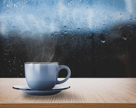 Blue cup with hot beverage near window on rainy day, space for text