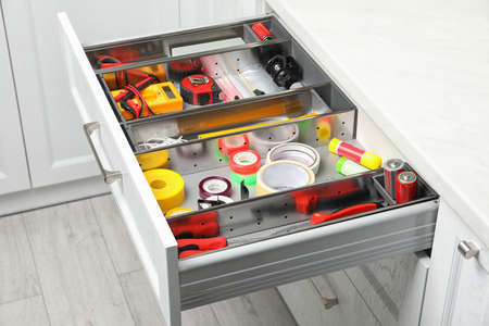 Set of instruments in open desk drawer indoors