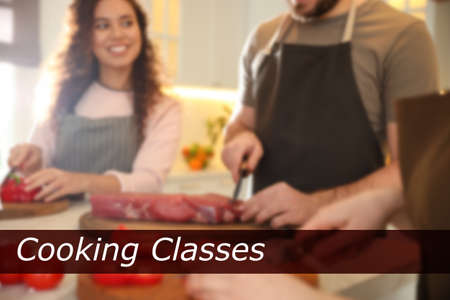 Cooking classes. Blurred view of people cutting meat and vegetables in kitchen