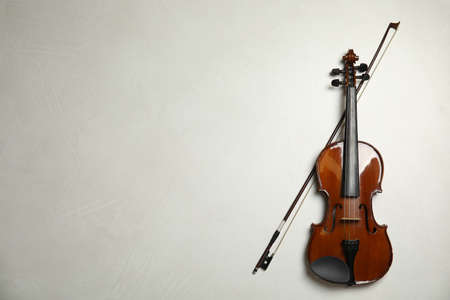 Beautiful violin and bow on grey stone table, flat lay. Space for text