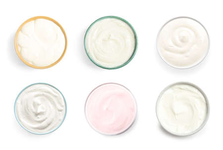 Set of delicious natural yogurts in bowls on white background, top view