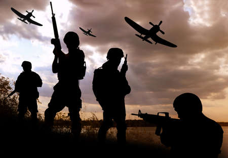 Silhouettes of soldiers with assault rifles and military airplanes patrolling outdoors Foto de archivo