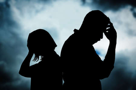 Silhouettes of arguing couple against sky with heavy rainy clouds. Relationship problems