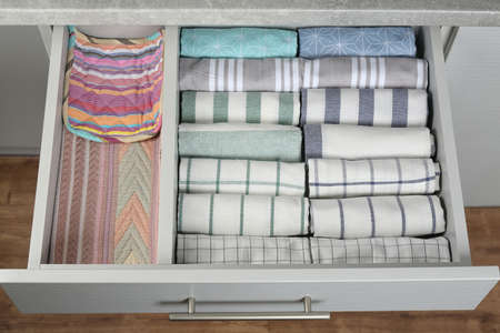 Open drawer with folded towels. Order in kitchen