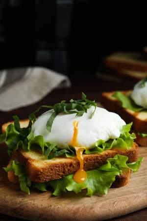 Delicious poached egg sandwich served on wooden board, closeup Banque d'images