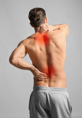 Man suffering from pain in neck and lower back on light grey background