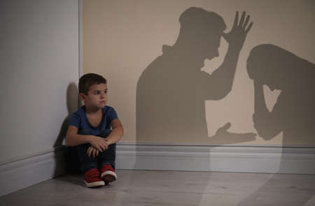 Little boy sitting in corner near yellow wall and silhouettes of arguing parents Stock Photo