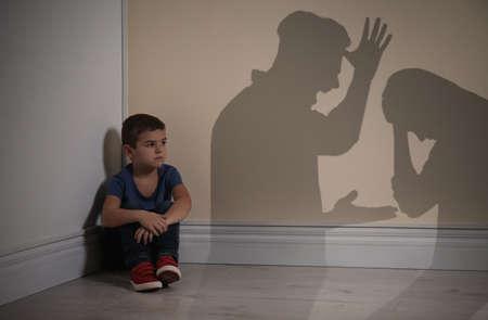 Petit garçon assis dans un coin près du mur jaune et silhouettes de parents se disputant Banque d'images