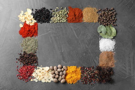 Frame made with different spices on grey background, flat lay. Space for text