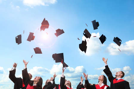 Happy students throwing graduation hats in air outdoors