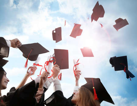 Étudiants heureux avec des diplômes jetant des chapeaux de remise des diplômes dans l'air à l'extérieur Banque d'images