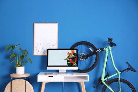 Stylish room interior with modern green bicycle and workplace