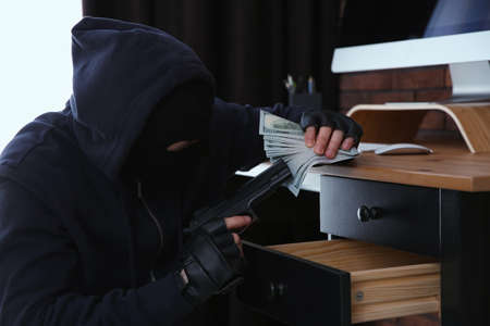 Dangerous masked criminal with gun stealing money from house