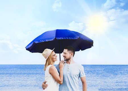 Happy romantic couple with umbrella for sun protection near sea Reklamní fotografie