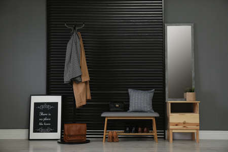 Hallway interior with modern furniture, mirror and clothes Stock Photo