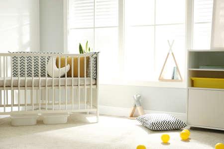 Cute baby room interior with crib and big window Stockfoto