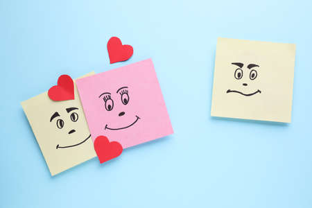 Paper notes with drawn faces on light blue background, flat lay. Concept of jealousy