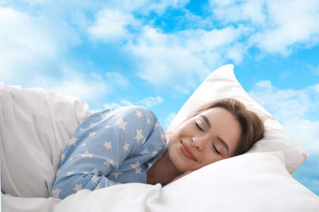 Young woman sleeping in bed. Blue sky on background