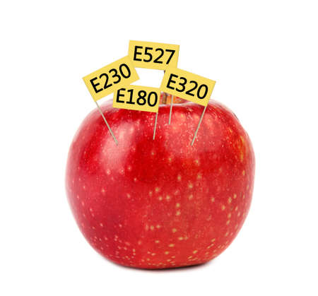 Fresh apple with E numbers isolated on white. Harmful food additives