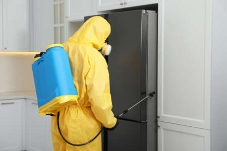 Pest control worker in protective suit spraying insecticide near refrigerator indoors Banque d'images