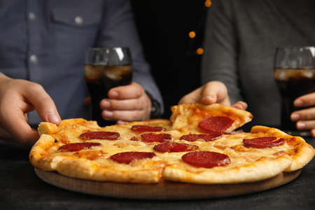 Friends taking tasty pepperoni pizza at table, closeup