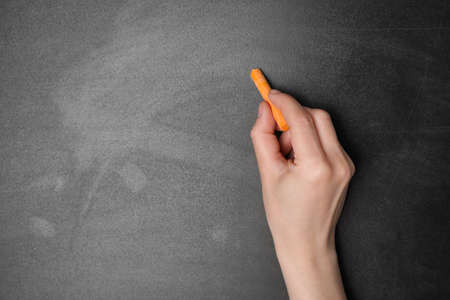 Woman with orange chalk near blackboard, closeup. Space for text
