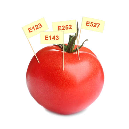 Fresh tomato with E numbers isolated on white. Harmful food additives