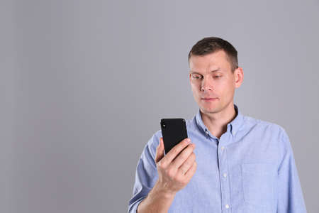 Man unlocking smartphone with facial scanner on grey background, space for text. Biometric verification