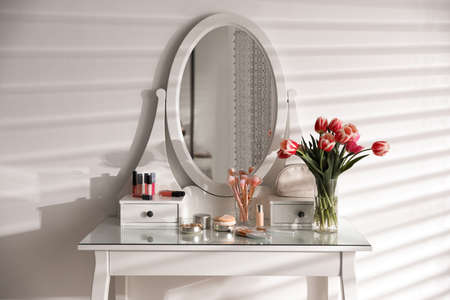 Elegant dressing table with makeup products, accessories and tulips indoors. Interior element Archivio Fotografico