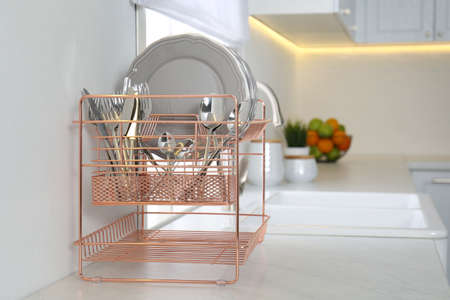 Clean dishes on drying rack in modern kitchen interior