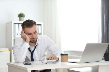 Lazy young man with calculator at table in office