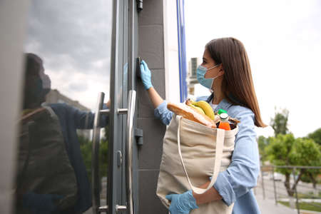 Female volunteer with products ringing doorbell outdoors. Aid during coronavirus quarantine
