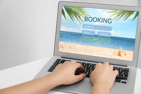 Woman using laptop to plan trip, closeup. Travel agency website