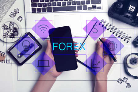 Woman with smartphone and laptop working at table, top view. Forex trading