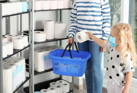 Little girl with medical mask and mother buying toilet paper in shop