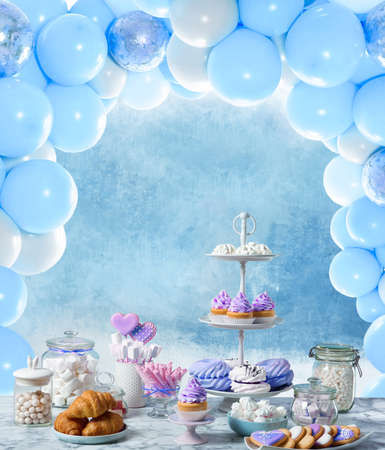 Baby shower party for boy. Tasty treats on table in room decorated with balloons Banque d'images