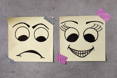 Paper notes with drawn faces on grey background, flat lay. Concept of jealousy